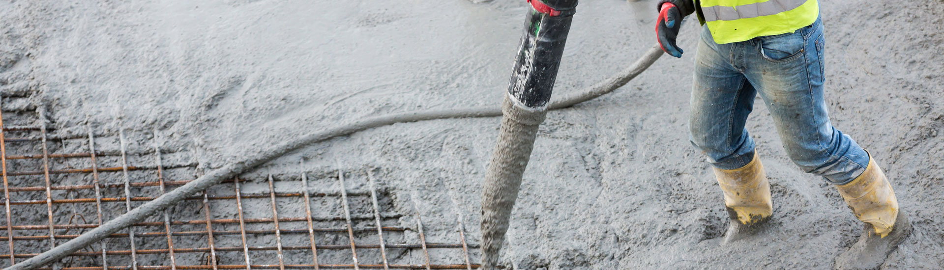 Worker Pouring Concrete with Pump Tube